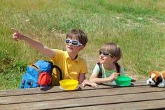 Två barn med ett ryggsäcksammanträde på en trätabell royaltyfria bilder