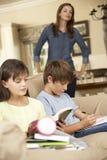 Två barn med läxasammanträde på Sofa At Home Whilst Mother klockor Arkivfoton