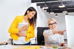 Två barn och mogna kontorskvinnor som har ett kläckning av ideermöte arkivbilder