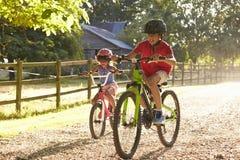Två barn på cirkulering rider tillsammans royaltyfri foto