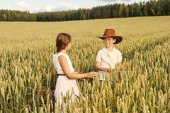 Två barn pojke och flicka undersöker öron av havre på ett vetefält royaltyfri bild