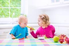 Två barn som äter yoghurt Arkivfoton