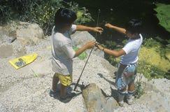 Två barn som agnar krokar och fiske, Malibu, CA Arkivfoto