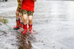 Två barn som bär röda regnkängor som hoppar in i en pöl Arkivbild