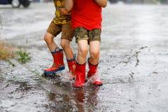 Två barn som bär röda regnkängor som hoppar in i en pöl Fotografering för Bildbyråer