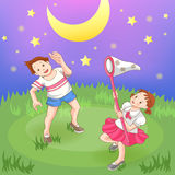 Två barn som fångar stjärnorna. Arkivbild