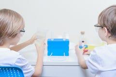 Två barn som gör vetenskapsexperiment books isolerat gammalt för begrepp utbildning Fotografering för Bildbyråer