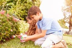 Två barn som har påskägget Hunt In Garden Arkivbilder