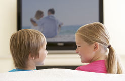 Två barn som hemma håller ögonen på Widescreen TV Royaltyfri Bild