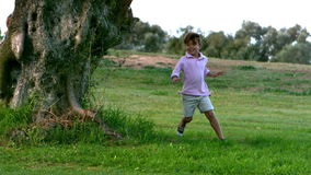 Två barn som kör runt om ett träd som spelar att jaga
