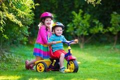 Två barn som rider cyklar arkivbild