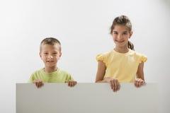 Två barn som rymmer ett blankt tecken Royaltyfri Foto