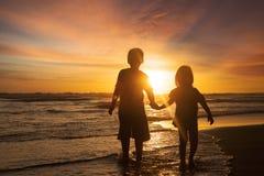 Två barn som rymmer händer på stranden Fotografering för Bildbyråer