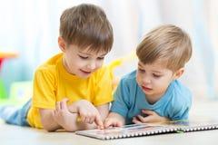 Två barn som ser boken Arkivbilder