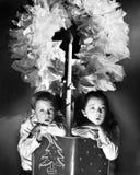 Två barn som sitter under en krans som rymmer en julberättelsebok (alla visade personer inte är längre uppehälle och ingen godsex Royaltyfria Bilder