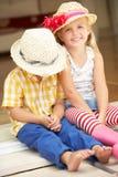 Två barn som sitter utanför hus arkivbilder