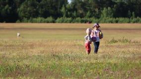 Två barn som spelar med en boll i fältet arkivfilmer