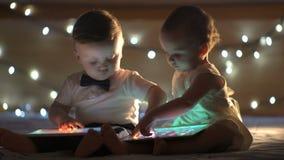 Två barn som spelar med en minnestavla stock video