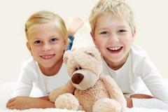 Två barn som spelar med en nallebjörn fotografering för bildbyråer