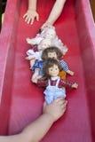 Två barn som spelar med fem dockor royaltyfria foton