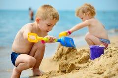 Två barn som spelar med sand på havstranden arkivfoto