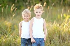 Två barn som spelar på äng arkivfoto