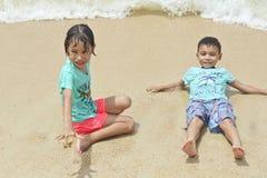 Två barn som spelar på stranden i Thailand royaltyfri fotografi