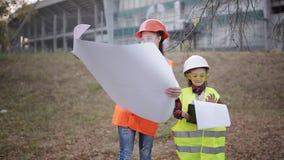 Två barnflickor i konstruktionshjälmar som ser det vita arket av papper eller att dra och att le arkivfilmer