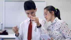 Två barnskolastudenter som arbetar på en vetenskap, projekterar tillsammans i kemiklassrum lager videofilmer