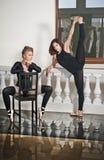 Två behagfulla ballerina, en som gör splittringarna, och en som sitter på stol, på marmorgolvet Ursnygga balettdansörer arkivbild