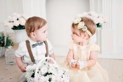 Två behandla som ett barn bröllop - pojken och flickan som kläs som brud och brudgum Royaltyfri Bild