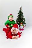 Två behandla som ett barn pojkar som kläs som Santa Claus och Santas honom arkivbild