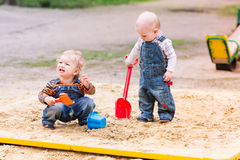 Två behandla som ett barn pojkar som spelar med sand Royaltyfri Fotografi