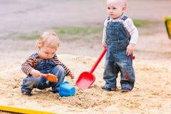 Två behandla som ett barn pojkar som spelar med sand i en sandlåda Fotografering för Bildbyråer