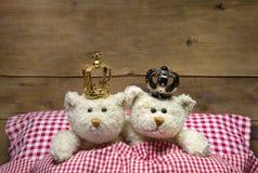 Två beigea nallebjörnar som ligger i rutig säng med kronor. Arkivbild