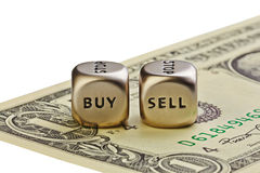 Två belägger med metall tärnar med uttrycker köp och Sell på en-dollar räkningisola royaltyfri bild