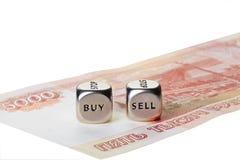 Två belägger med metall tärnar med uttrycker köp och Sell på fem tusen rouble arkivbild