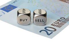 Två belägger med metall tärnar med uttrycker köp och Sell på tjugo-euro sedel Royaltyfri Bild