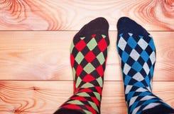 Två ben i olika brokiga sockor på ett trägolv royaltyfri foto
