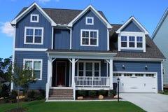 Två-berättelse blått, förorts- hem i en grannskap i North Carolina fotografering för bildbyråer