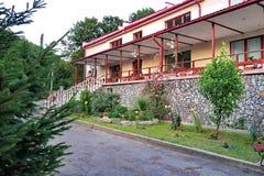 Två-berättelse byggnad med en röd avloppsränna och ett staket som dekoreras med blommor royaltyfri bild
