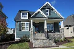 Två-berättelse förorts- hem med en stenfarstubro i en grannskap i North Carolina fotografering för bildbyråer