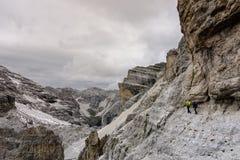 Två bergsbestigare på en utsatt avsats i dolomitesna Royaltyfria Foton
