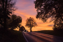 Två bilar på den lantliga vägen med bilbillyktan på på solnedgången Arkivbilder