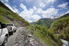 Två bilar på en slingrande väg i bergen, bergmaxima i snön och bakgrund för gröna kullar royaltyfri fotografi