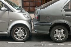 Två bilar parkerade mycket nästan i en europeisk stad royaltyfria foton