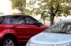 Två bilar som är röda och som är gråa i parkeringsplatsen av ett träd arkivbilder