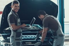 Två bilmekaniker som arbetar i service för auto reparation royaltyfri fotografi