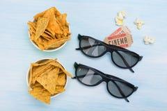 Två biobiljetter, en pappers- kopp med nachos och 3 D-exponeringsglas för att hålla ögonen på en film på en ljus bakgrund royaltyfria bilder