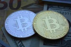 Två Bitcoin mynt ligger på bakgrunden av valutaräkningar arkivfoton